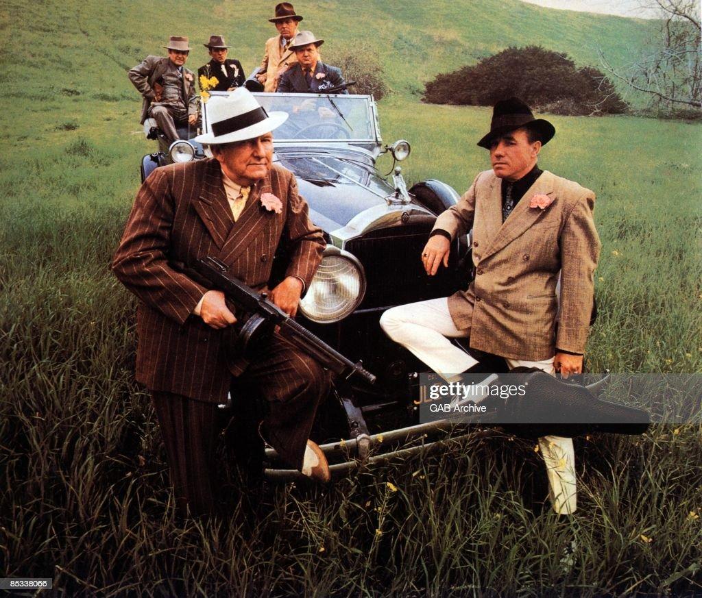 Photo of Earl SCRUGGS and Lester FLATT and FLATT & SCRUGGS; posed, in field, dressed as gangsters