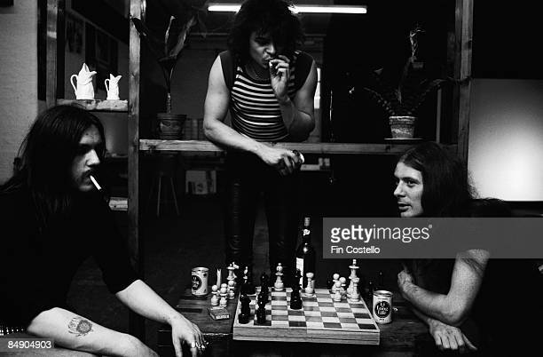 Photo of Eddie CLARKE and LEMMY and MOTORHEAD and Phil TAYLOR Group portrait playing chess LR Lemmy Phil Taylor and Eddie Clarke