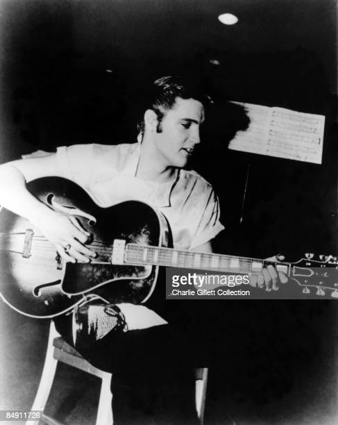 USA Photo of Elvis PRESLEY Playing guitar Sitting on stool With sheet music behind c1956
