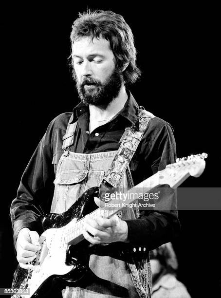 Photo of Eric CLAPTON performing live onstage playing 'Blackie' Fender Stratocaster guitar wearing dungarees c1974