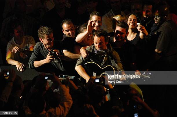 HALL Photo of FANS and Bruce SPRINGSTEEN being touched and surrounded by fans in audience performing live onstage on Devils And Dust tour