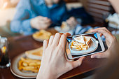 Photo of female hands using smartphone to photograph her lunch