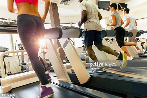 Photo of four young people running on treadmill