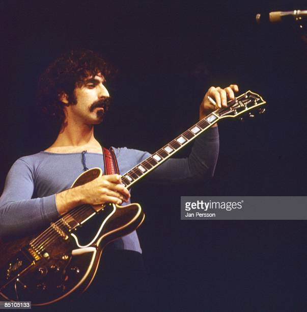 Photo of Frank ZAPPA Frank Zappa performing on stage putting a cigarette under the strings of a Gibson guitar