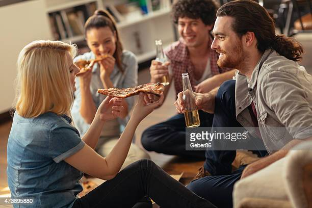 Photo of friends eating pizza and drinking beer at home
