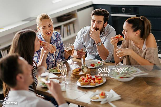 Photo of friends enjoying appetisers and wine at home