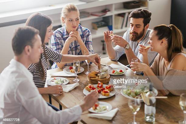 Photo of friends enyoing appetizers and white wine