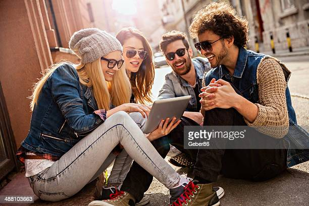 Photo of friends sitting on sidewalk looking at tablet