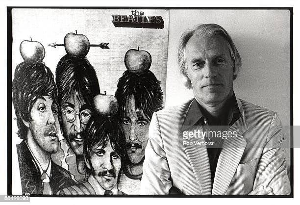 Photo of George MARTIN posed with poster of Beatles