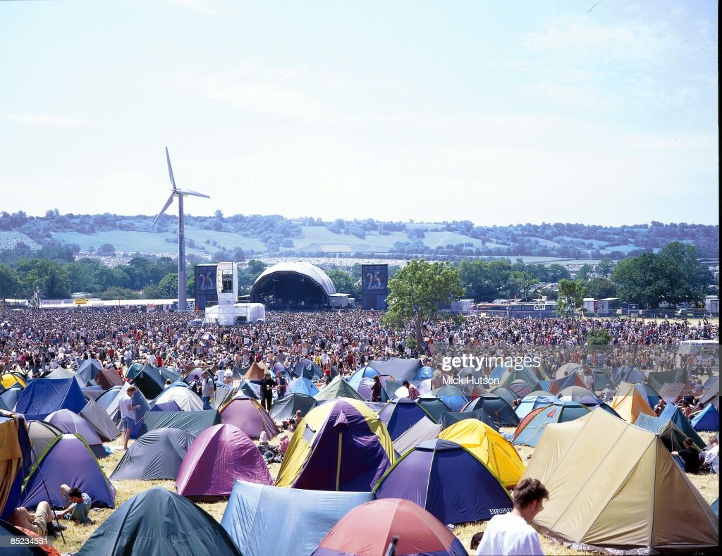 FESTIVAL Photo of GLASTONBURY, Wide view of the main stage at Glastonbury Festival, showing tents, crowds and generator wind turbine