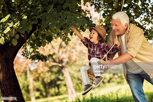 Photo of grandfather pushing grandson on a swing