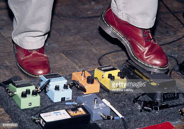 Photo of GUITAR EFFECTS PEDALS Bank of guitar effects pedals in use on stage including Boss Ibanez and MXR pedals using wahwah pedal