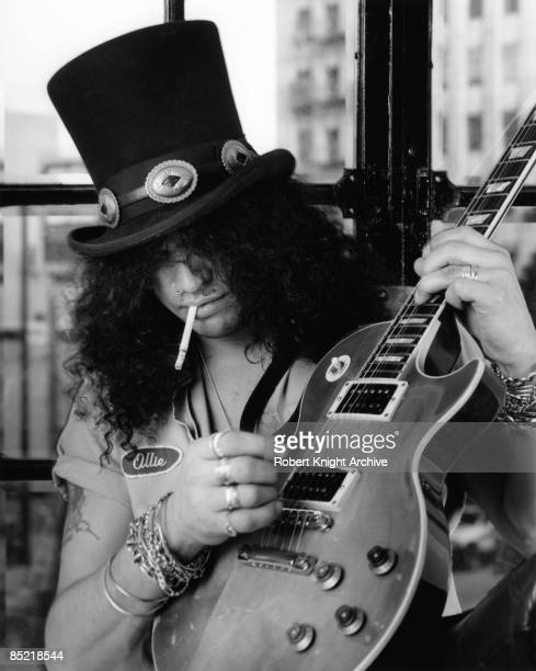 Photo of GUNS AND ROSES and GUNS ROSES and GUNS N' ROSES and SLASH Slash posed studio smoking cigarette holding Gibson Les Paul guitar