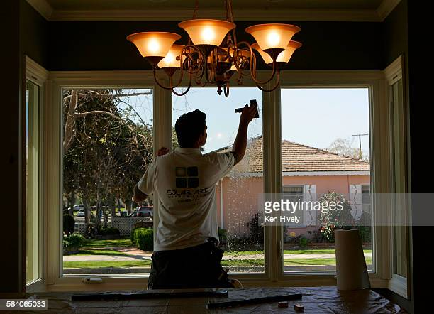 Photo of installer Jamie Bailey of Solar Art putting solar film on window of a house in Culver City Story about adding solar film to insulate windows...