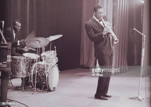 HALL Photo of John COLTRANE and Elvin JONES Drummer Elvin Jones and John Coltrane performing on stage