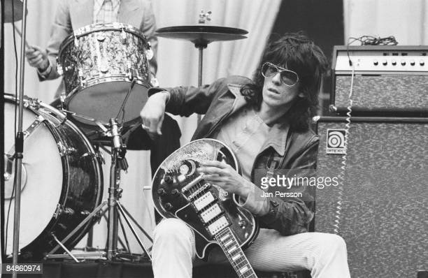 Photo of Keith RICHARDS and ROLLING STONES Keith Richards sitting on drum riser onstage during soundcheck wearing sunglasses holding Gibson Les Paul...