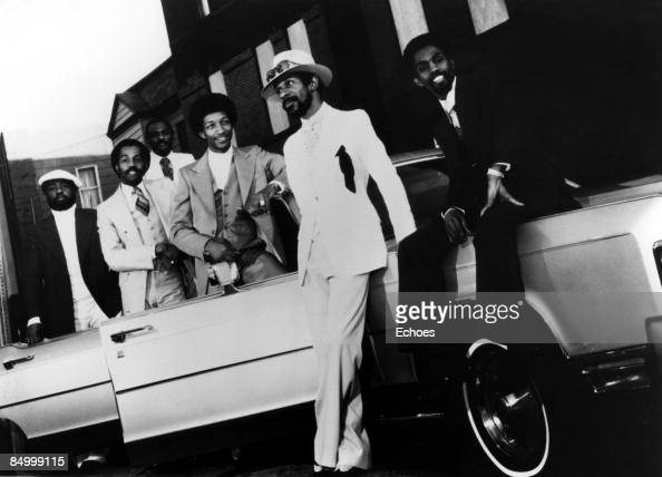 Photo of KOOL THE GANG Posed group portrait of Kool and the Gang leaning on a cadillac car