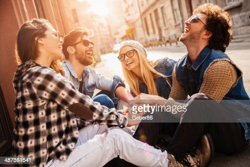 Photo of laughing friends joining hands outdoors