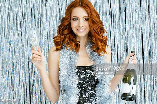 Photo of laughing girl holding bottle of champagne