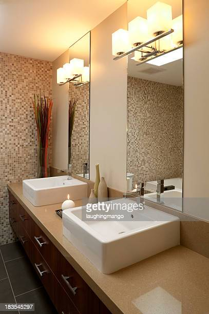 Photo of lit bathroom with modern his and hers sinks