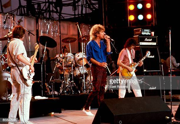 Photo of LIVE AID and LED ZEPPELIN and Robert PLANT and Jimmy PAGE LR John Paul Jones Phil Collins Robert Plant Jimmy Page performing live onstage at...