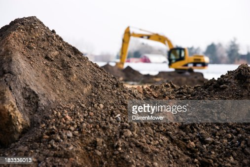 Photo of machinery and dirt piles during winter construction