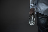 It is a problem. Close up of stylish man wearing casual clothes keeping bottle with beverage in hand while standing isolated on grey background