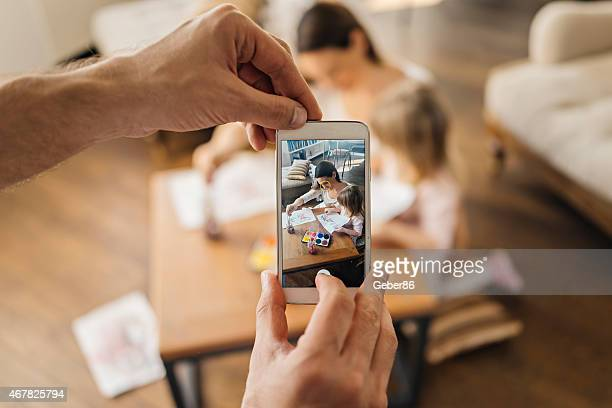 Photo of male hands using smartphone to photograph family playing