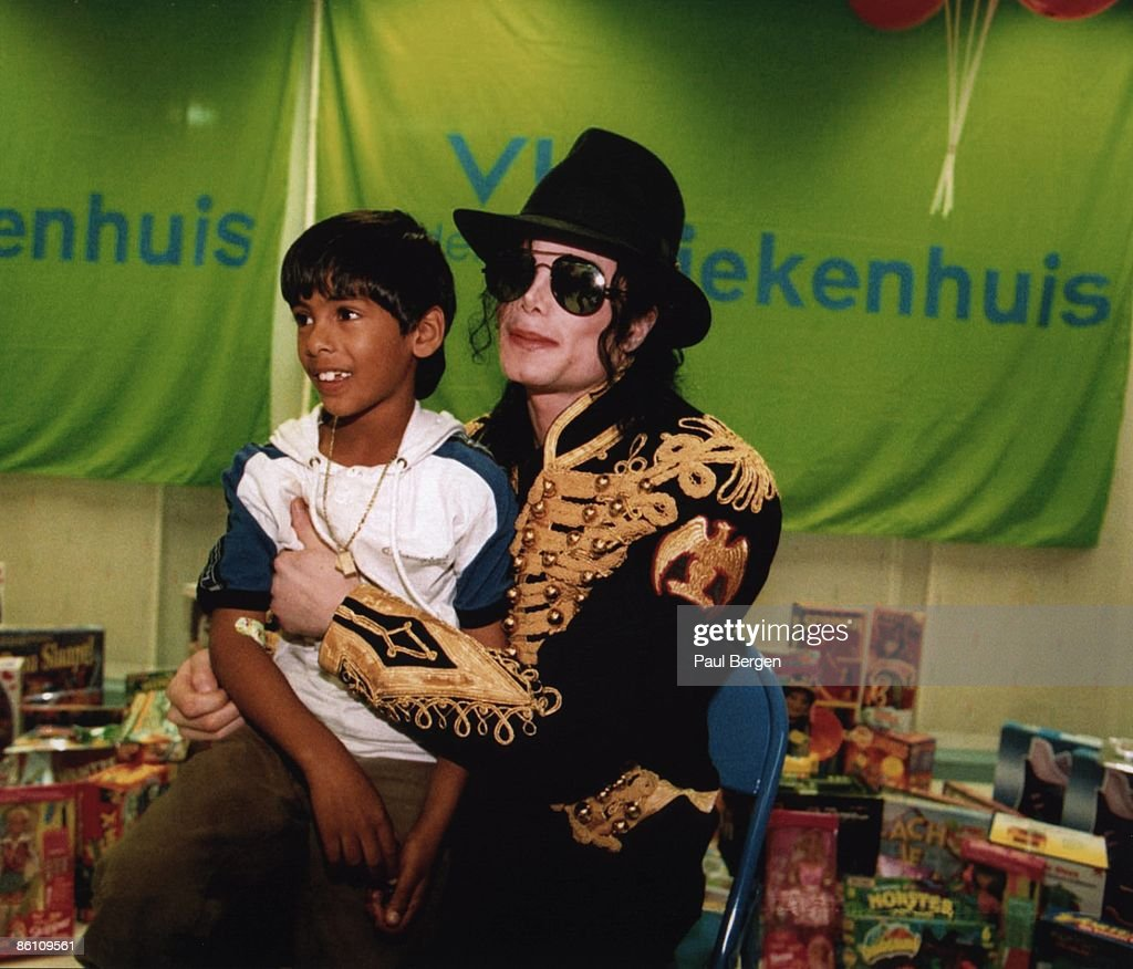 Photo of Michael JACKSON; Michael Jackson with a child sat on his lap, sunglasses