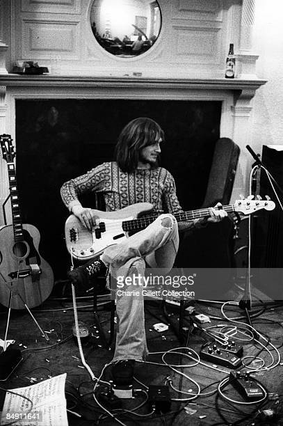 Photo of Mike OLDFIELD Posed in studio sitting on chair playing bass Surrounded by guitar effects pedals and leads