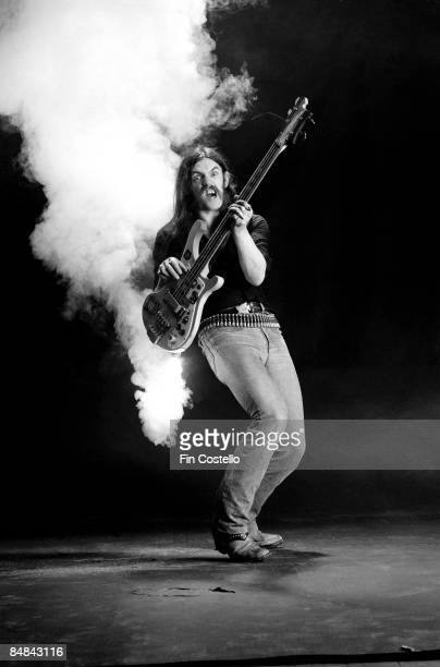 Photo of MOTORHEAD and LEMMY Lemmy posed studio with firework attached to bass