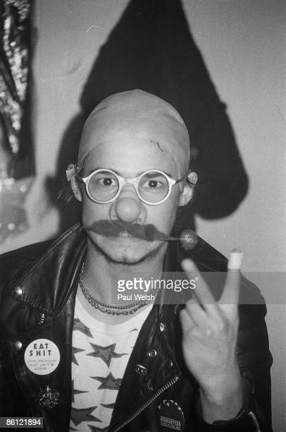Photo of MOTORHEAD Phil 'Philthy Animal' Taylor backstage at the Electric Circus wearing bald wig and fake moustache gesturing