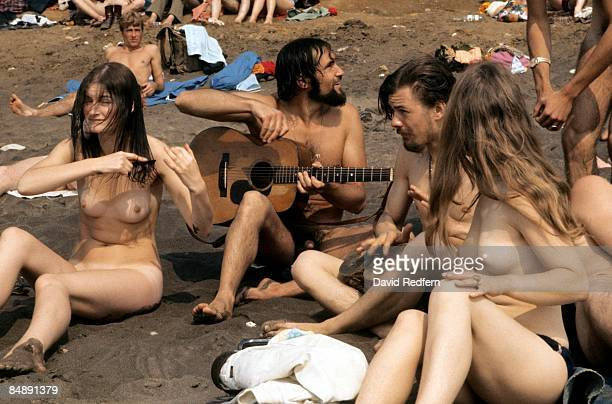 Photo of NAKED and HIPPIES and FANS and FESTIVALS naked hippies sit on the beach on the Isle of Wight during the festival