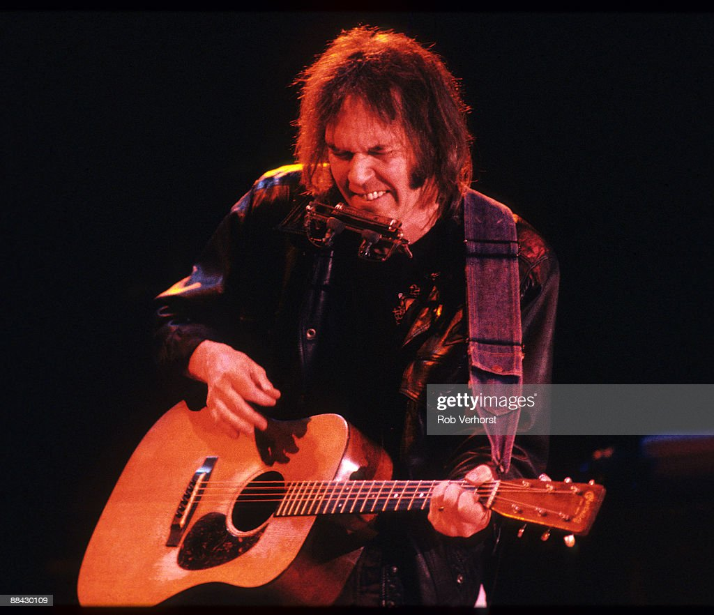 AHOY Photo of Neil YOUNG, Neil Young performing on stage, playing acoustic guitar and harmonica