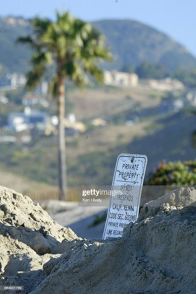 Photo of no tresspass sign and sand berm where the homeowners of Broad Beach Malibu infamous for no–trespassing/private beach signs have bulldozed...