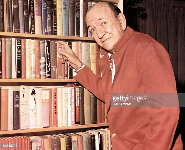 Photo of Noel COWARD posed at bookshelf