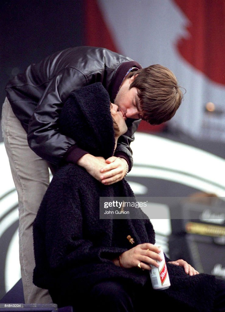 Photo of OASIS and Liam GALLAGHER and Noel GALLAGHER; Noel Gallagher & Liam Gallagher, kissing, on stage at Glasgow Green Festival