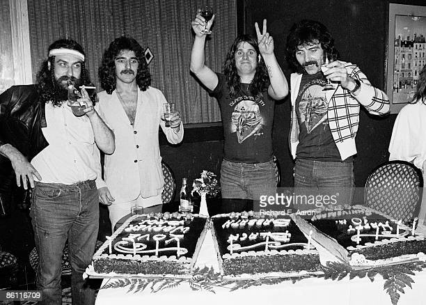 Photo of Ozzy OSBOURNE and BLACK SABBATH LR Bill Ward Geezer Butler Ozzy Osbourne Tony Iommi posed group shot drinking with tenth anniversay cakes