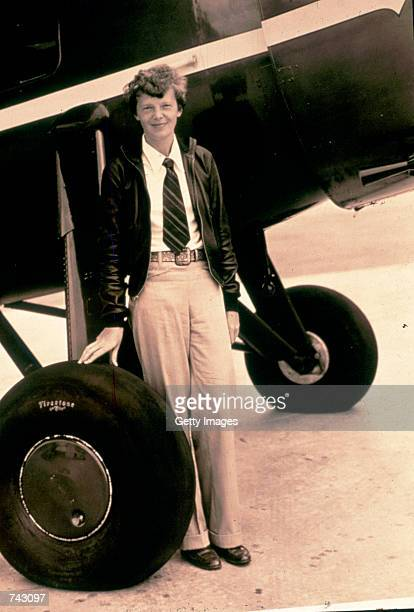 Photo of pilot Amelia Earhart standing by her plane