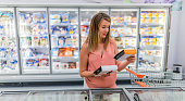 Caucasian pregnant brown hair woman buying frozen food in local supermarket, female checking food labeling.
