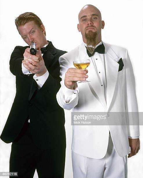 Photo of QUEENS OF THE STONE AGE and Josh HOMME and Nick OLIVERI LR Josh Homme Nick Oliveri posed studio drinking champagne holding gun wearing...