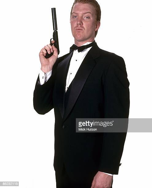 Photo of QUEENS OF THE STONE AGE and Josh HOMME Josh Homme posed studio holding gun wearing tuxedo dressed as James Bond