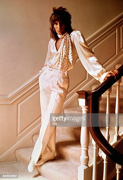 Photo of Rod STEWART posed studio portrait of Rod Stewart wearing polka dot scarf full length standing at the bottom of staircase solo era