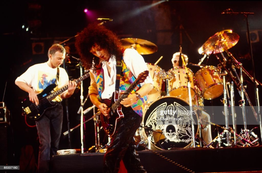 STADIUM Photo of Roger TAYLOR and QUEEN and John DEACON and Brian MAY, L-R John Deacon, Brian May and Roger Taylor performing on stage at the Freddie Mercury Tribute concert