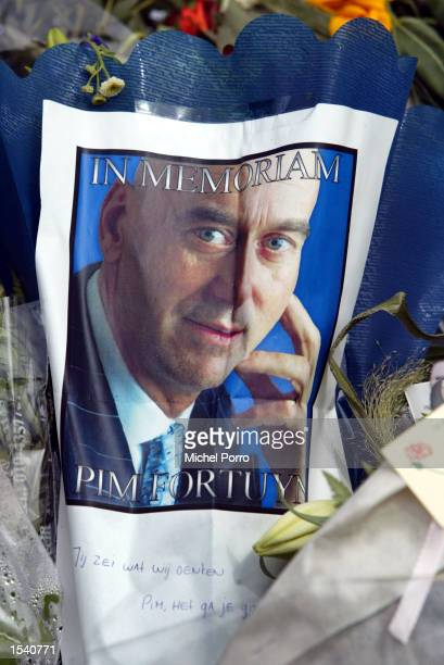 A photo of slain Dutch politician Pim Fortuyn lies amid flowers outside his house May 9 2002 in Rotterdam Netherlands Written underneath the photo is...