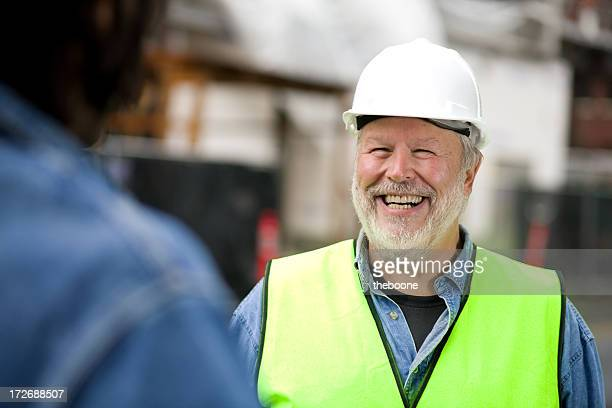 Photo of smiling bearded construction worker in green vest