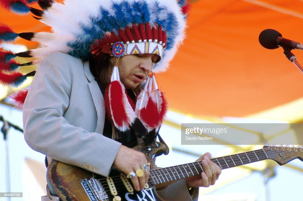 FESTIVAL Photo of Stevie Ray VAUGHAN, performing live onstage, playing Fender Stratocaster guitar (Number One), wearing headdress
