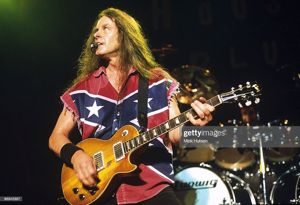 Photo of Ted NUGENT; performing live onstage, wearing confederate flag jacket, playing Gibson Les Paul guitar