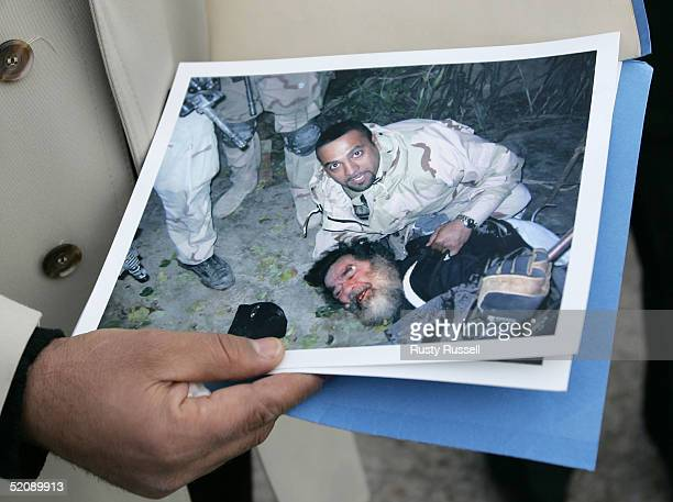 A photo of the capture of Saddam Hussein subdued during his capture by US Special Forces translator Samir is displayed by a companion of Samir near...
