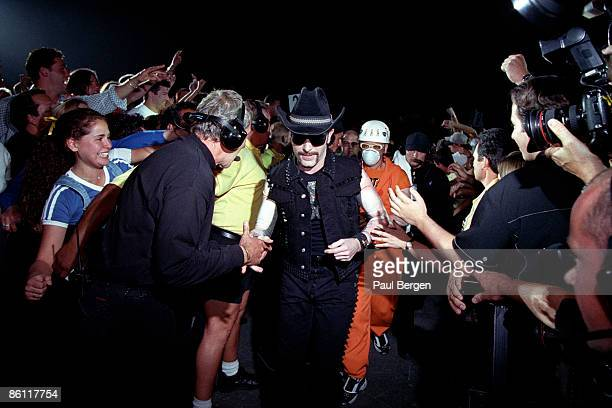 Photo of THE EDGE and U2 The Edge and Adam Clayton walking through the crowds to the stage on first date of the PopMart Tour